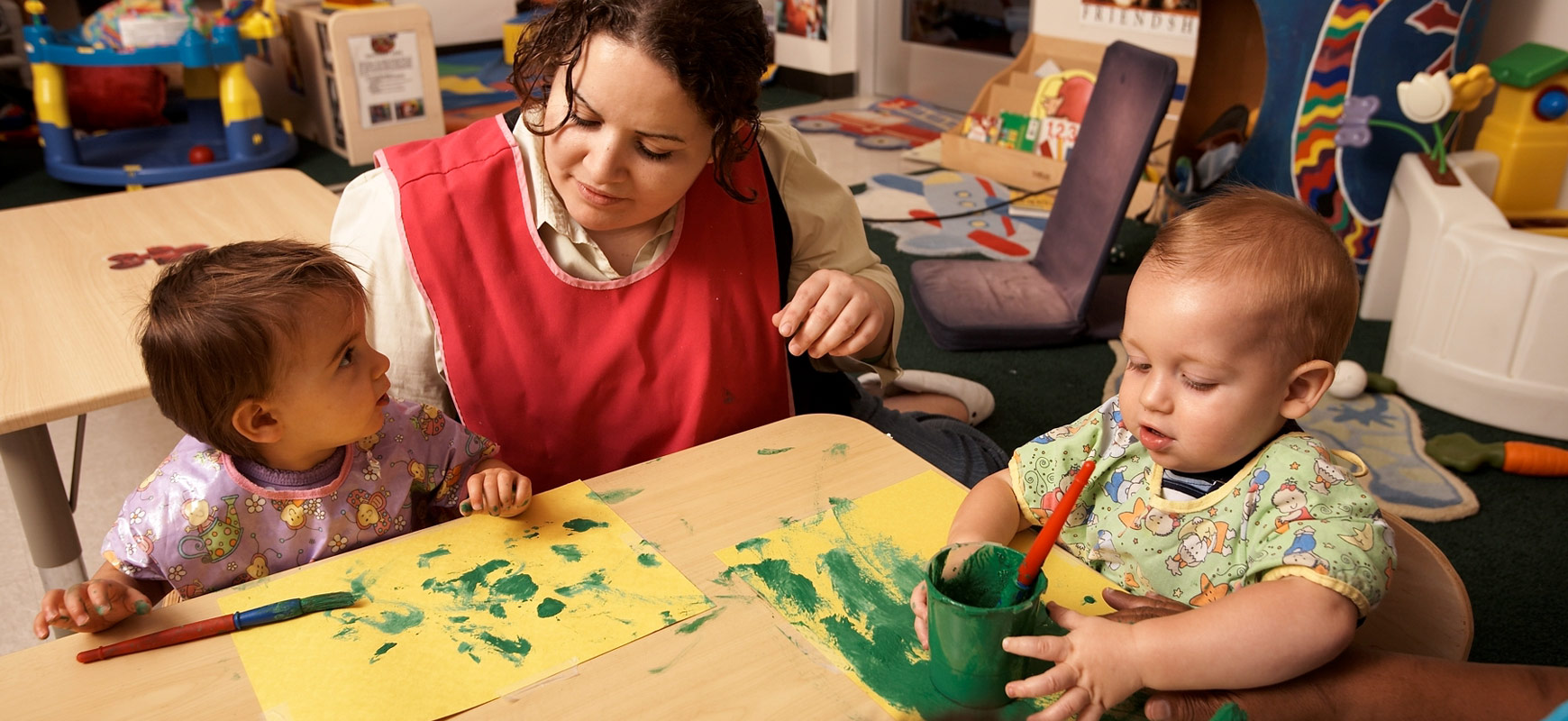 toddlers finger painting with teachers